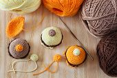 pic of thread-making  - Making of handmade colorful crochet toys sweets with skein on wooden table - JPG