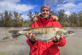 stock photo of game-fish  - Happy fisherman with big fish - JPG