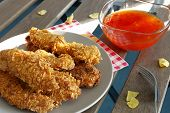 stock photo of strip  - chicken strips on plate and chilli sauce - JPG