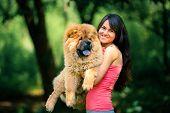 image of dog park  - girl holding a dog on a background of park - JPG