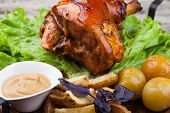picture of roasted pork  - Appetizing roast pork knuckle on cutting board - JPG