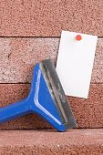 pic of gad  - White piece of paper next to a blue chisel - JPG