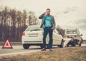 picture of tow-truck  - Man calling while tow truck picking up his broken car  - JPG