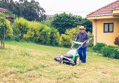 pic of grass-cutter  - Portrait of young man with straw hat and plaid shirt mowing lawn with a lawnmower machine - JPG
