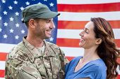 image of reunited  - Handsome soldier reunited with partner against an american flag - JPG