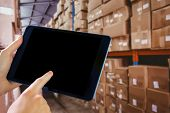 foto of forklift driver  - Man using tablet pc against forklift in large warehouse - JPG
