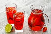 stock photo of refreshing  - Refreshing summer drink with Strawberry in jug and glasses on the vintage wooden table