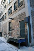 pic of windows doors  - An alley door and a small porch a railing of a large brick building - JPG