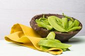 stock photo of snow peas  - Snow peas on wooden bowl with green napkin on wooden table - JPG