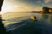image of kayak  - Young lady paddling the kayak in a calm lagoon - JPG