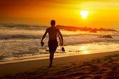 stock photo of board-walk  - Surfer walking with board along the beach - JPG