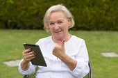 stock photo of lawn chair  - Senior serene woman wearing white shirt and sitting on a chair on the green lawn of the garden while using a wireless black tablet PC and showing thumb up in a warm day of summer - JPG