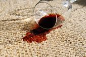 stock photo of glass-wool  - A glass of red wine spilt on a pure wool carpet - JPG