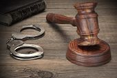 Handcuffs, Judge Gavel And Old Law Books On Wooden Table poster