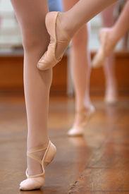 stock photo of ballet dancer  - legs and slippers of classical ballet dancers rehearsing - JPG
