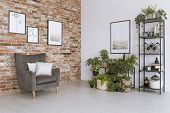 Grey Armchair Against Brick Wall poster