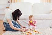 Постер, плакат: Привлекательная женщина играя с ребенком в сидя на ковер в гостиной