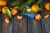 Tangerine gift and fir on a wooden background. Christmas and new year card space for your text.