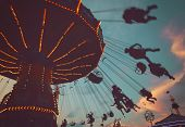 a local fair at dusk with people riding swinging rides and enjoying the summer atmosphere toned with poster