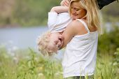 picture of tickle  - A mother tickling and playing with excited happy son in a green meadow - JPG