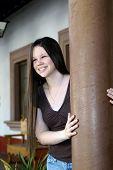 pic of hacienda  - Female teen leans against a pillar on the front porch of a Mexican hacienda - JPG