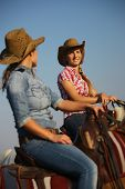 Country girls - women riding horse. Two young country girls sitting on horseback, looking at each ot poster