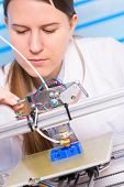 A female student or laboratory assistant in the automation laboratory is debugging the work of the 3 poster