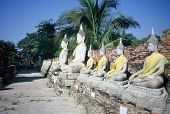 Images Of The Meditating Buddha Sits Serenely In A Row In Front Of The Ruins Of A Chedi At Wat Yai C poster
