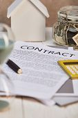 Selective Focus Of House Model , Contract And Moneybox, Real Estate Concept poster