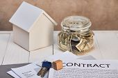 House Model On White Wooden Table Near Moneybox, Keys And Contract, Real Estate Concept poster