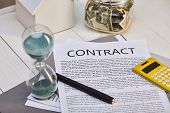 House Model, Contract With Pen, Hourglass And Moneybox On White Wooden Table, Real Estate Concept poster