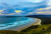 Evening twilight on the sandy beach. Fantastic New Zealand. The picturesque Pacific coast of the Sou poster