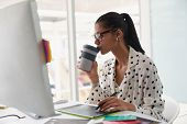 Front view of beautiful mixed-race female graphic designer having coffee while using graphic tablet  poster