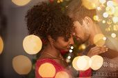 Romantic couple in sweaters dancing before new year eve at home. Young lovely man and african woman  poster