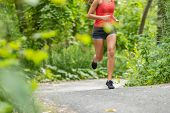 Running athlete woman on run path jogging closeup of lower body thighs, legs, running shoes in fores poster