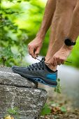 Running shoes sports smartwatch man tying shoe laces. Male fitness runner getting ready to jog in sp poster