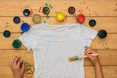 The Girl Begins To Paint A White T-shirt In The Style Of Tie Dye. Staining Fabric In Tie Dye Style. poster
