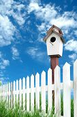 image of bird fence  - white fence with bird house and blue sky - JPG