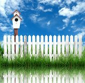 stock photo of bird fence  - white fence with bird house and blue sky - JPG