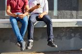 Two Friends Enjoying Leisure Outside, Using Smartphones, Consulting Internet. Cropped Portrait Of Tw poster