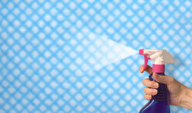 stock photo of house cleaning  - female hand spraying cleaning polish over a cloth background - JPG