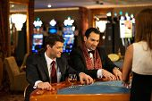 stock photo of roulette table  - Two young cheerful men behind table in a casino - JPG