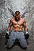 Young boxer with angel wings behind his back standing on his knee