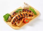 grilled sausages with vegetable side dish on a wooden cutting board