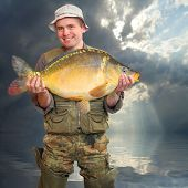 The fisherman with big fish (The Mirror Carp - Cyprinus Carpio). Success concept.