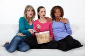 Three woman eating popcorn whilst watching film