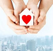 charity, real estate and family home concept - closeup picture of male and female hands holding whit