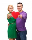 couple, love and family concept - smiling couple holding big red heart