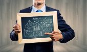 Close up of businessman holding frame with business sketches