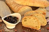 Fresh bread - ciabatta, chili, olives on wooden background